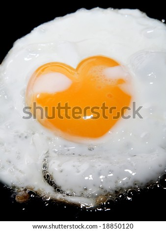 cooking frying egg with heart shape yolk on black - stock photo