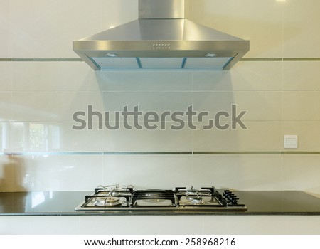 cooking gas stove with hood in modern kitchen - stock photo