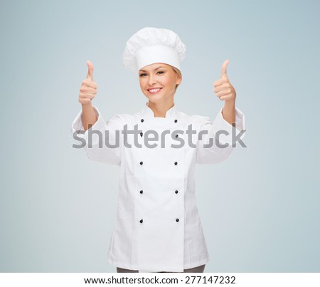 cooking, gesture and food concept - smiling female chef, cook or baker showing thumbs up over gray background - stock photo