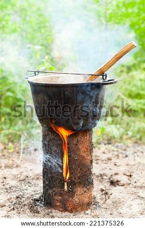 Cooking Goulash soup in cauldron on Finnish (Swedish) log stove - stock photo