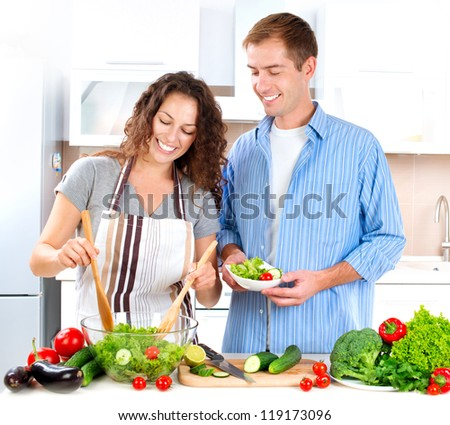 Cooking.Happy Couple Cooking Together - Man and Woman in their Kitchen at home Preparing Vegetable Salad.Diet.Dieting. Healthy Food - stock photo