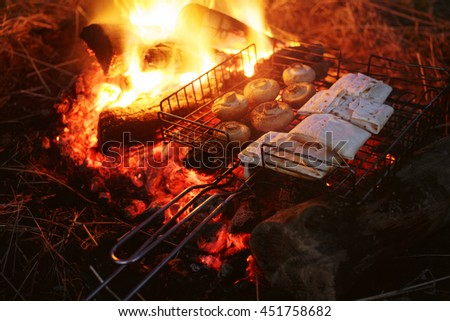 Cooking healthy food on fire in wilderness. Cheese and mushrooms grilled on campfire - stock photo