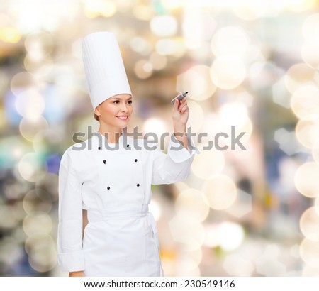 cooking, holidays, advertisement and people concept - smiling female chef, cook or baker with marker writing something on virtual screen over lights background - stock photo