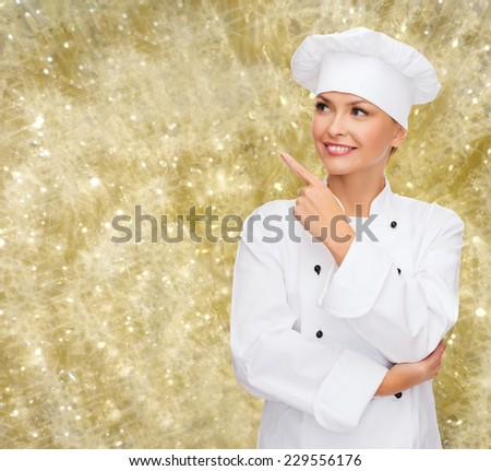 cooking, holidays and people concept - smiling female chef, cook or baker pointing finger up over yellow lights background - stock photo