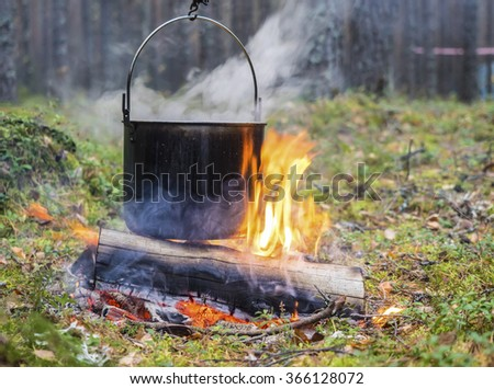 Cooking in sooty cauldron on campfire at forest. From a kettle there is steam. Close up - stock photo
