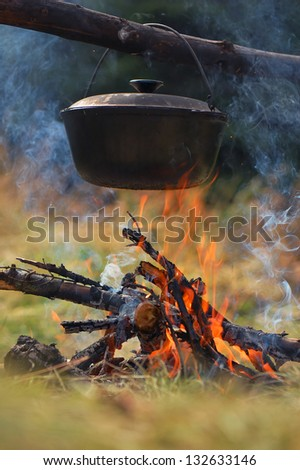 Cooking in the mountains. Cauldron on fire - stock photo