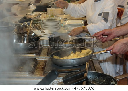 Cooking inside Restaurant's Kitchen, Pans, Dishes and Chef with Uniform