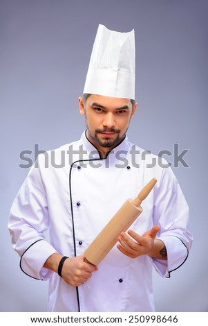 Cooking is a passion. Portrait of young handsome cook in uniform holding a rolling pin with serious face expression while standing over grey background with copy space - stock photo