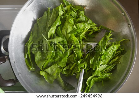 "Cooking Japanese spinach or ""Po Chai"" on the wok - stock photo"