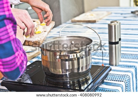 Cooking of dumplings or noodles made of mashed potatoes, eggs, and flour.  Father and children preparing dinner. The process of throwing dough into boiling water.