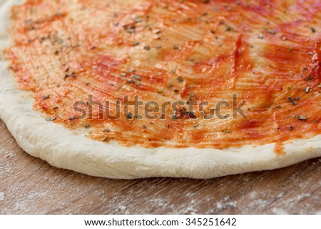 Cooking of the pizza dough, covered with sauce and seasonings - stock photo