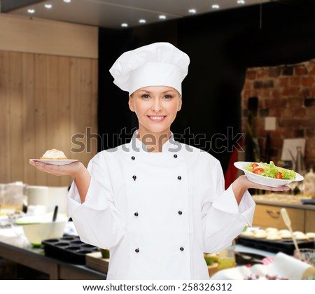cooking, people and food concept - smiling female chef, cook or baker with salad and cake on plates over restaurant kitchen background - stock photo