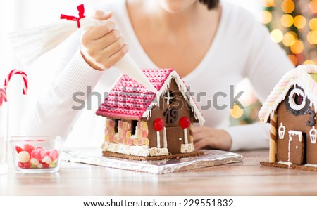 cooking, people, christmas and decoration concept - happy woman making gingerbread houses at home - stock photo