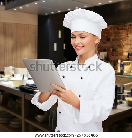 cooking, people, technology and food concept - smiling female chef, cook or baker with tablet pc computer over restaurant kitchen background - stock photo
