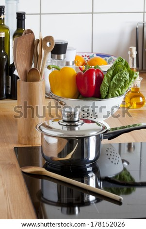 Cooking Pot and Cooking Spoon on Ceramic Hob and other Kitchen Utensils - stock photo