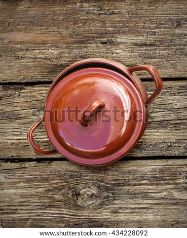 cooking pot on old wooden table background - stock photo