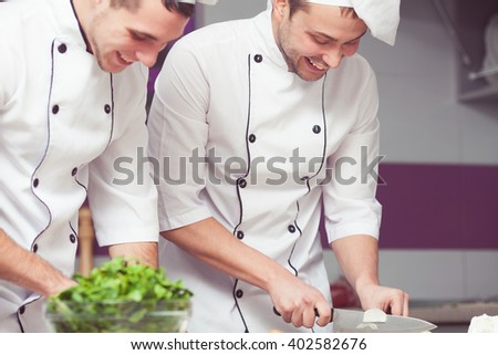 Cooking process concept. Portrait of two laughing working men in cook uniform making food in modern kitchen. Indoor shot