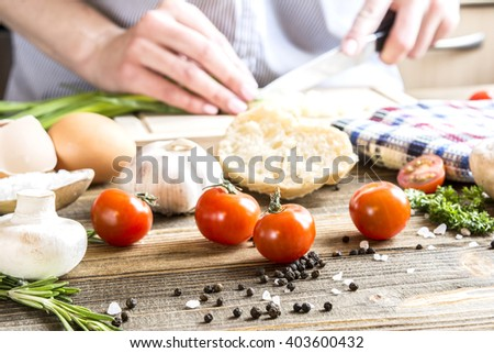 cooking process in the kitchen cherry tomatoes close-up on background female hands chopped green