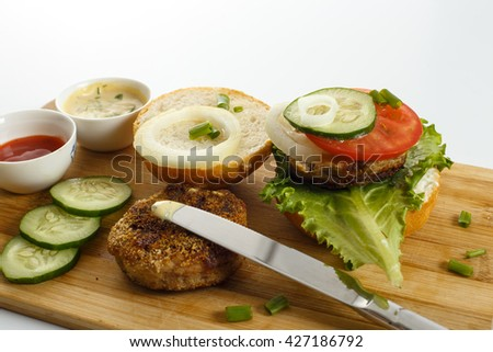 Cooking process of a sandwich burger, ingredients on cutting board on wooden table against white background, fresh vegetables, herbs, fried meat, buns, sauces and knife, horizontal view, shallow DOF - stock photo