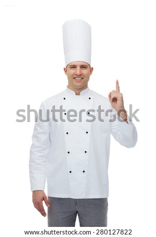 cooking, profession, advertisement and people concept - happy male chef cook pointing finger up to something - stock photo