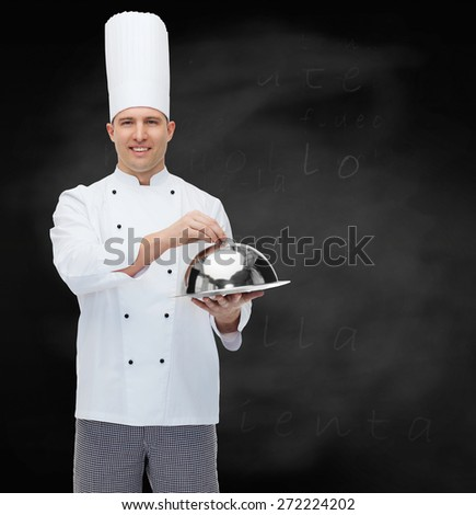 cooking, profession and people concept - happy male chef cook holding cloche over black chalk board background - stock photo
