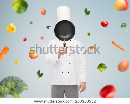 cooking, profession and people concept - male chef cook covering face or hiding behind frying pan over gray background with falling vegetables - stock photo