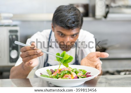cooking, profession, cuisine, food and people concept - happy male chef cook decorating dish salad - stock photo