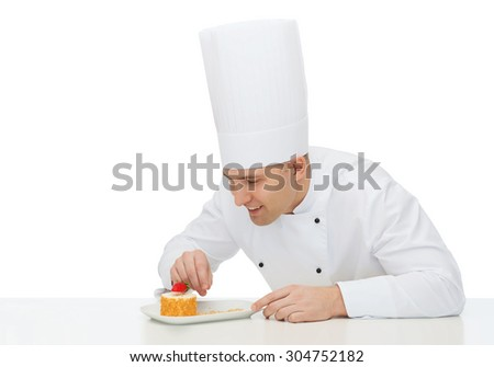cooking, profession, haute cuisine, food and people concept - happy male chef cook decorating dessert - stock photo