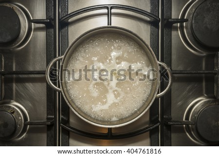 Cooking rice in pan with water with chicken stock - stock photo
