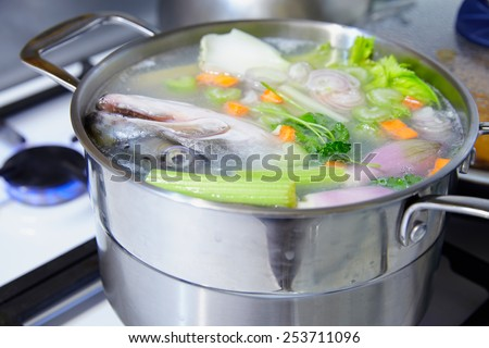 Cooking salmon fish broth with a vegetables - stock photo