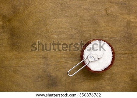 Cooking salt in a wooden shaker with measuring spoon. - stock photo