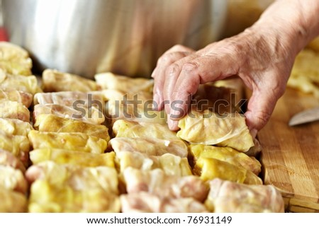 Cooking sarmale, a traditional Romanian dish, with grinded meat and rice wrapped in boiled cabbage leaves - stock photo