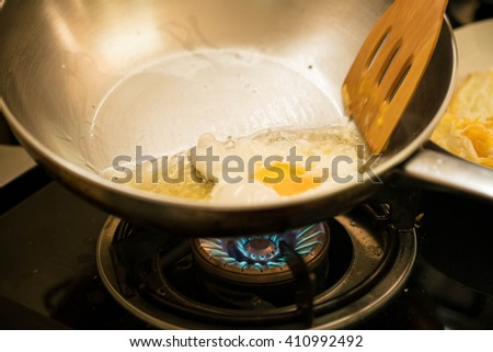 cooking scene ; frying egg in a frying pan & wooden spade of frying pan   - stock photo