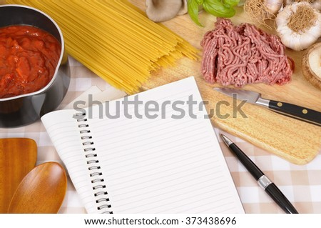Cooking spaghetti bolognese, ingredients, blank open recipe book, copy space - stock photo