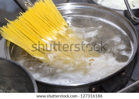 cooking spaghetti in the kitchen of the restaurant - stock photo