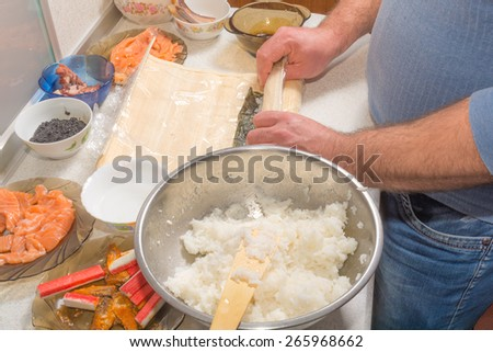 Cooking sushi at home with nori, salmon, avocado, rice and cucumber. - stock photo