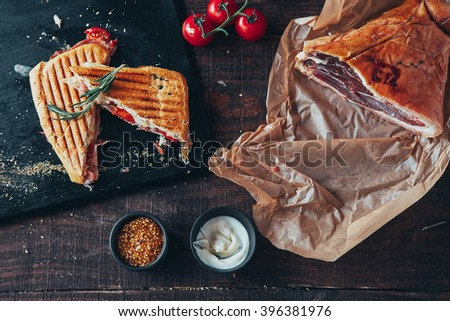 cooking tasty panini with ham covered with cheese, tomatoes and flavoring - stock photo