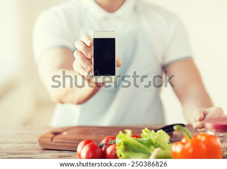 cooking, technology, advertising and home concept - close up of male hands holding smartphone with blank black screen - stock photo