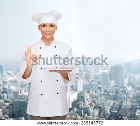 cooking, technology and people concept - smiling female chef, cook or baker with tablet pc computer showing ok gesture over city background - stock photo