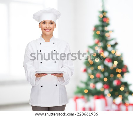 cooking, technology, holidays and people concept - smiling female chef, cook or baker with tablet pc computer over living room and christmas tree background - stock photo