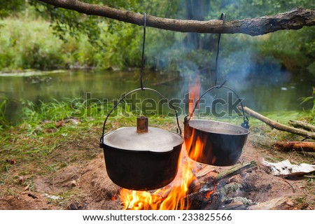 Cooking the meal in a kettle on the camp fire:River rafting expedition. Poland - stock photo