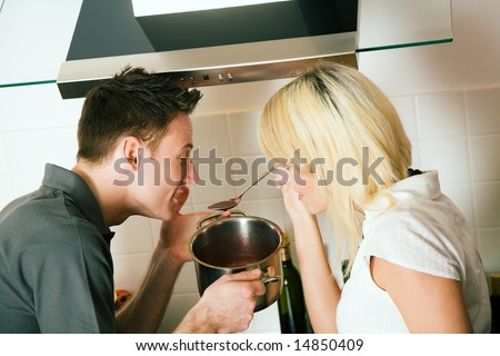 Cooking together: tasting the sauce - stock photo
