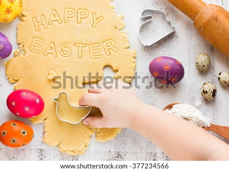 Cooking traditional Easter biscuits. Kid hands cut cookie from raw dough on a white table with colorful eggs and cake cutters. Easter food concept - stock photo