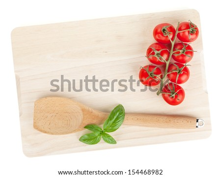Cooking utensil and tomato with basil over cutting board. Isolated on white background - stock photo
