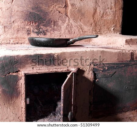 Cooking with a frying pan on old russian stove in a village house - stock photo