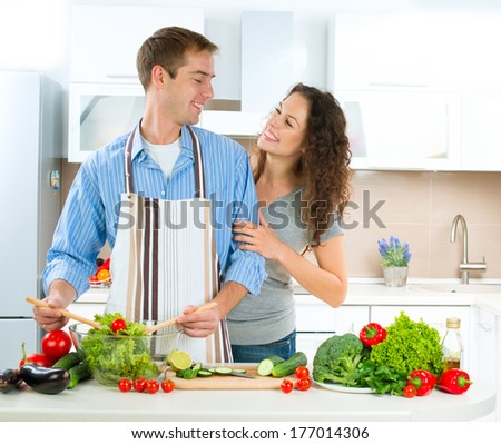 Cooking. Young Man cooking. Happy Couple Cooking Together - Man and Woman in their Kitchen at home Preparing Vegetable Salad. Diet. Dieting. Healthy Food Tasting  - stock photo