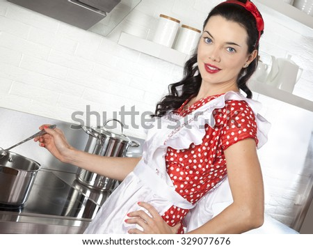 Cooking young woman in kitchen stirring in pot making food for dinner - stock photo