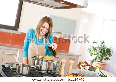 Cooking - Young woman with spaghetti on stove cooking Italian cousine - stock photo