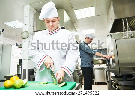 cooks chef in uniform cooking at restaurant kitchen  - stock photo