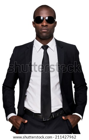 Cool and confident. Serious young African man in formalwear and sunglasses holding hands in pockets and looking at camera while standing isolated on white background  - stock photo